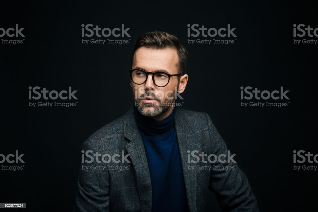Studio portrait of elegant man, dark background Portrait of handsome businessman in tweed jacket and glasses against black background, looking away. 30-39 Years Stock Photo