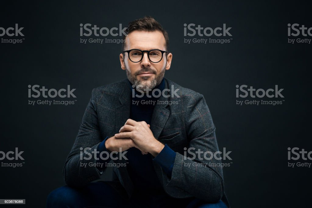 Studio portrait of elegant man, dark background Portrait of handsome businessman in tweed jacket and glasses sitting against black background, looking at camera. 30-39 Years Stock Photo