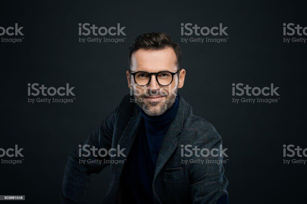 Studio portrait of elegant man, dark background Portrait of handsome businessman in tweed jacket and glasses against black background, smiling at camera. 30-39 Years Stock Photo