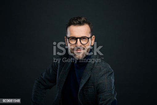 Portrait of handsome businessman in tweed jacket and glasses against black background, smiling at camera.