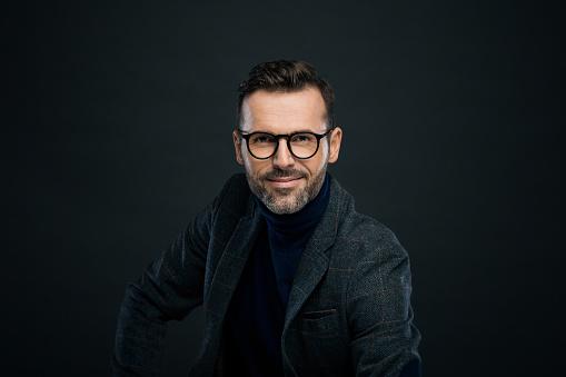 Portrait of handsome businessman in tweed jacket and glasses against black background, smiling at camera.