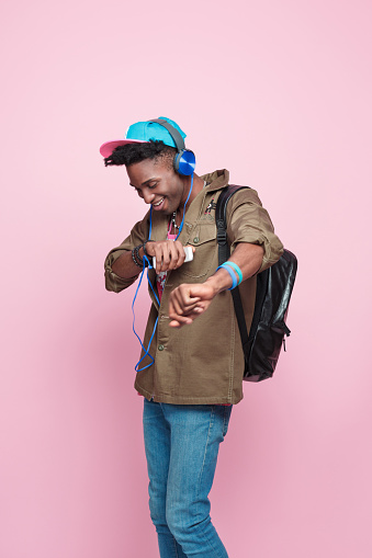 Summer portrait of happy, cool afro american young man in modern outfit, wearing headphone, cap, jacket and backpack, dancing against pink background.