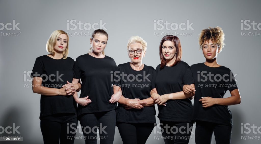 Studio portrait of happy confident women standing together Group of pleased women wearing black clothes, embracing against grey background and smiling at camera. Studio shot. Activist Stock Photo