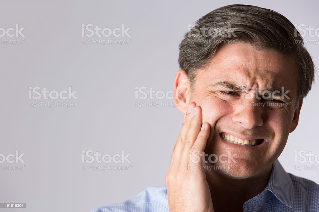 Studio Portrait Of Man Suffering With Toothache stock photo