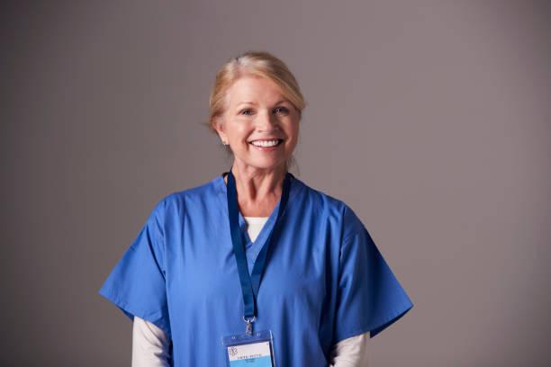 Studio Portrait Of Mature Female Nurse Wearing Scrubs Standing Against Grey Background stock photo