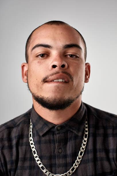 studio portrait of mixed race young man making funny face - gangster zdjęcia i obrazy z banku zdjęć