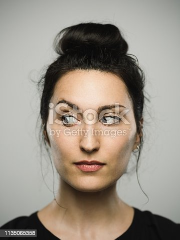 Close up portrait of mediterranean young woman looking to the side against gray white background. Vertical shot of caucasian real people observing in studio with long black hair and a hair bun. Photography from a DSLR camera. Sharp focus on eyes.
