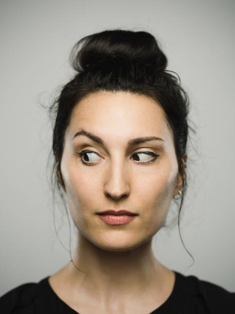 studio portrait of real mediterranean young woman looking to the side - cynic stock pictures, royalty-free photos & images