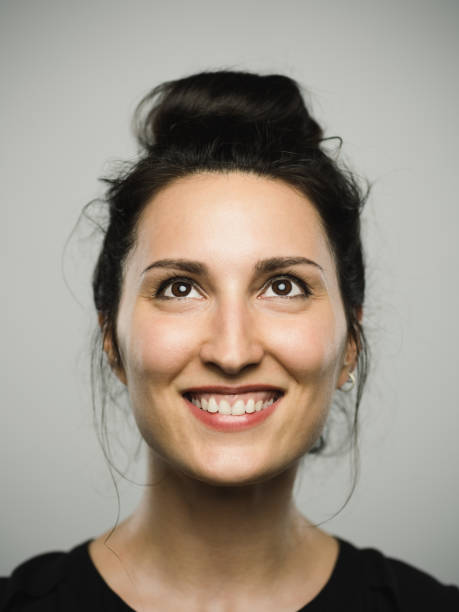 studio portrait of real mediterranean young woman with excited expression looking up - sud europeo foto e immagini stock