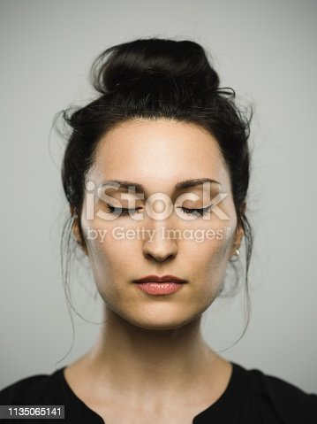 Close up portrait of mediterranean young woman with eyes closed against gray white background. Vertical shot of caucasian real people resting in studio with long black hair and a hair bun. Photography from a DSLR camera. Sharp focus on eyes.