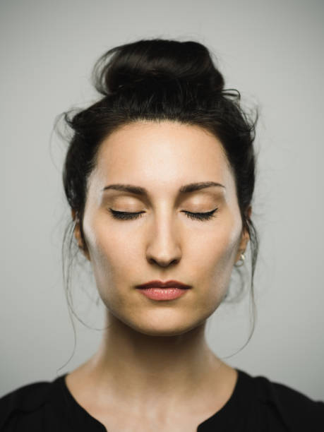 Studio portrait of real mediterranean young woman with eyes closed Close up portrait of mediterranean young woman with eyes closed against gray white background. Vertical shot of caucasian real people resting in studio with long black hair and a hair bun. Photography from a DSLR camera. Sharp focus on eyes. eyes closed woman stock pictures, royalty-free photos & images