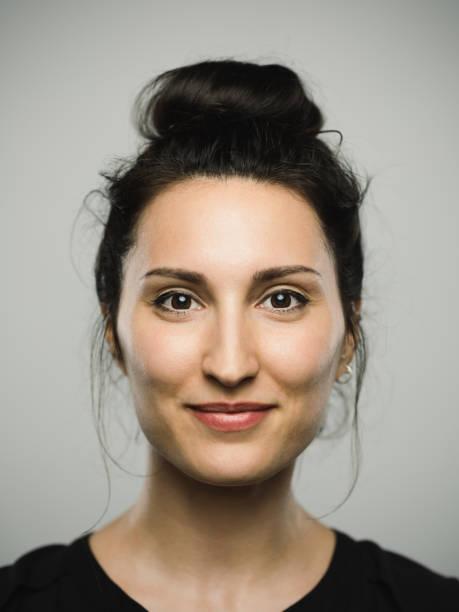 studio portrait of real mediterranean young woman with happy expression - sud europeo foto e immagini stock