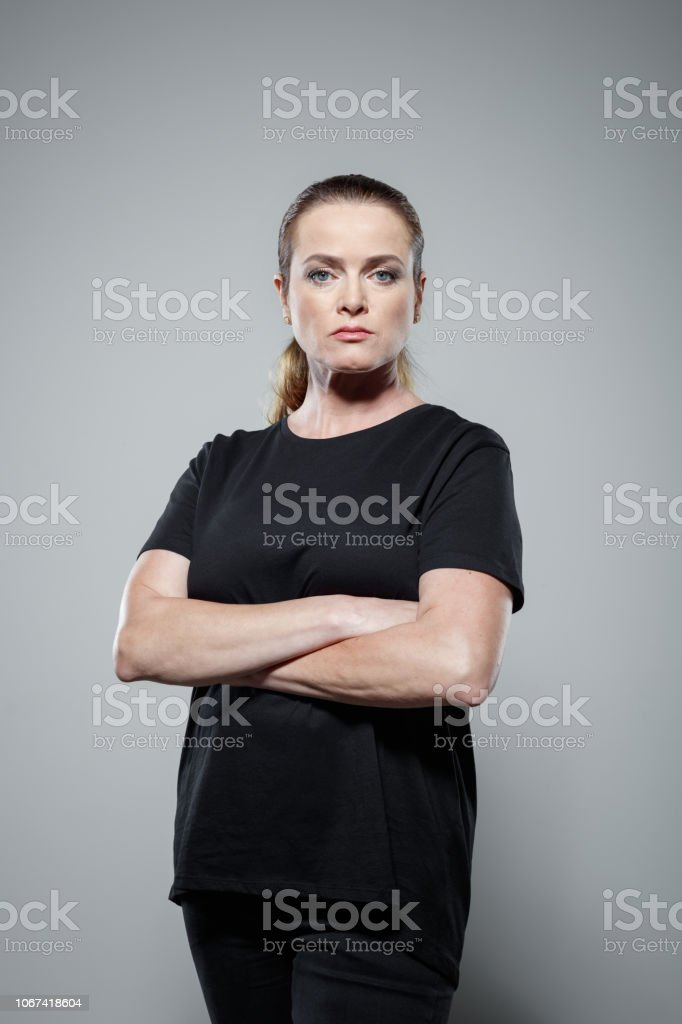 Studio portrait of sad woman Desperate woman wearing black clothes, standing with arms crossed against grey background, staring at camera. Studio shot. 35-39 Years Stock Photo