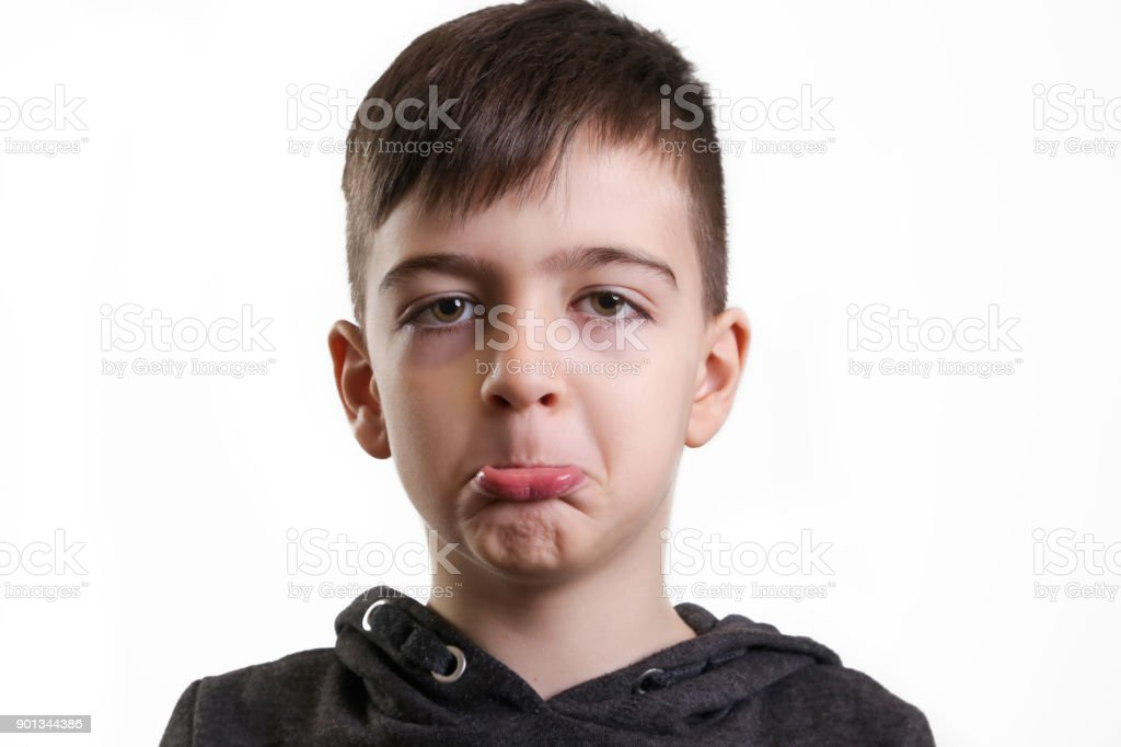 Studio portrait of smiling preschool boy on the white background - frowning facial expression stock photo