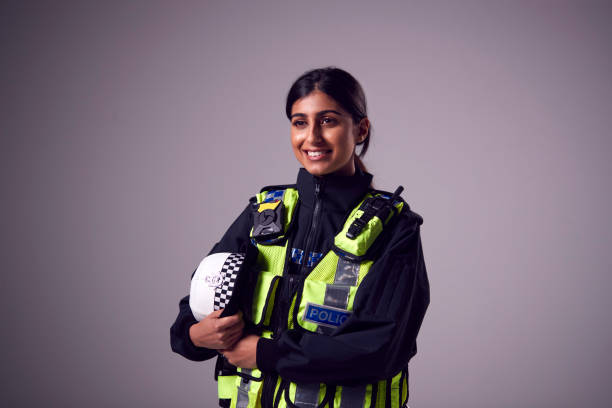 Studio Portrait Of Smiling Young Female Police Officer Against Plain Background stock photo