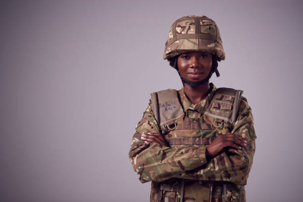 Studio Portrait Of Smiling Young Female Soldier In Military Uniform Against Plain Background stock photo