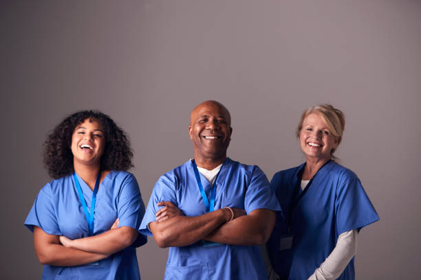 Studio Portrait Of Three Members Of Surgical Team Wearing Scrubs Standing Against Grey Background stock photo