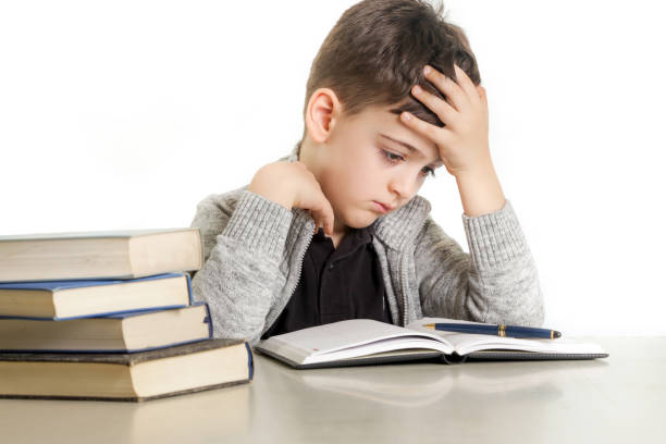 Studio portrait of young boy struggling with his homework - learning difficulties concept stock photo