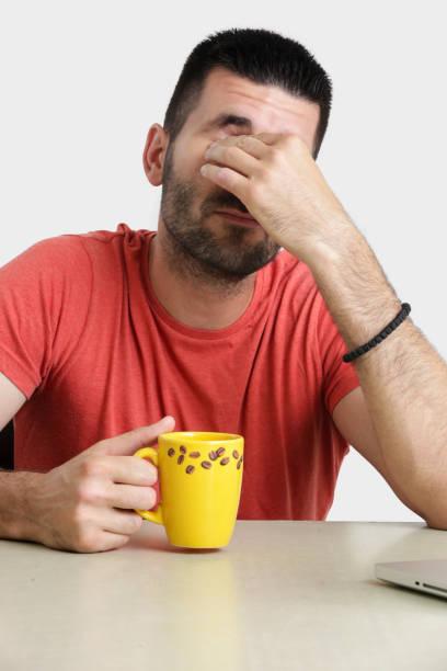 studio-porträt der schönen jungen mann mit tasse kaffee seine augen reiben, aufwachen, gefühl müde oder gelangweilt konzept - rot bekümmerte möbel stock-fotos und bilder
