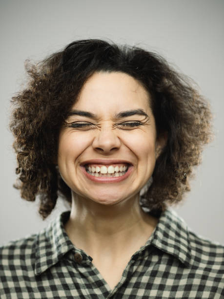 Studio portrait of young happy woman with excited expression and eyes closed Close-up portrait of young caucasian happy woman with excited expression and eyes closed. Vertical shot of hispanic real people laughing with long curly hair and green eyes. Photography from a DSLR camera. Sharp focus on eyes. grimacing stock pictures, royalty-free photos & images