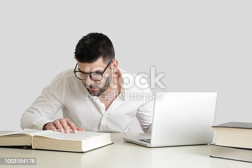 istock Studio portrait of young man reading a book in front of his laptop 1003154176