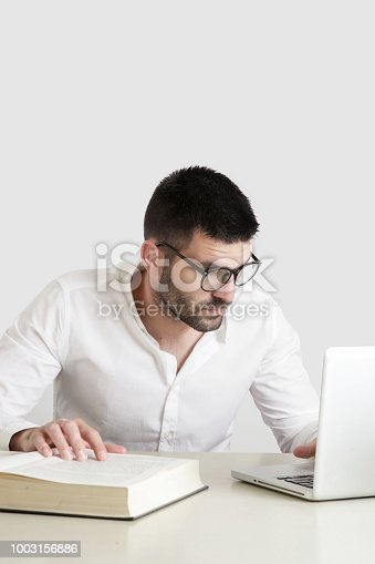 istock Studio portrait of young man reading a book in front of his laptop 1003156886