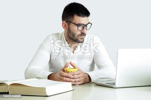 istock Studio portrait of young man reading a book in front of his laptop 1003156888