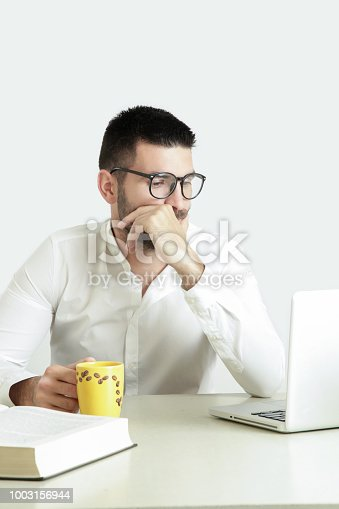 istock Studio portrait of young man reading a book in front of his laptop 1003156944