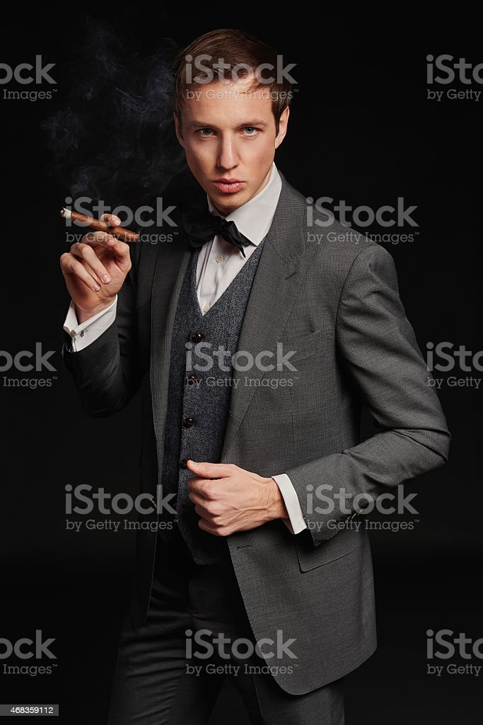Studio portrait of young man smoking a cigar royalty-free stock photo