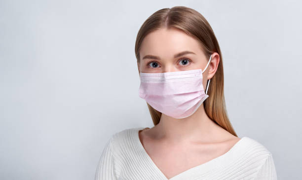 Studio portrait of young woman wearing a face mask, looking at camera, close up, isolated on gray background. Flu epidemic, dust allergy, protection against virus. City air pollution concept Studio portrait of young woman wearing a face mask, looking at camera, close up, isolated on gray background. Flu epidemic, dust allergy, protection against virus. Blonde woman costume stock pictures, royalty-free photos & images