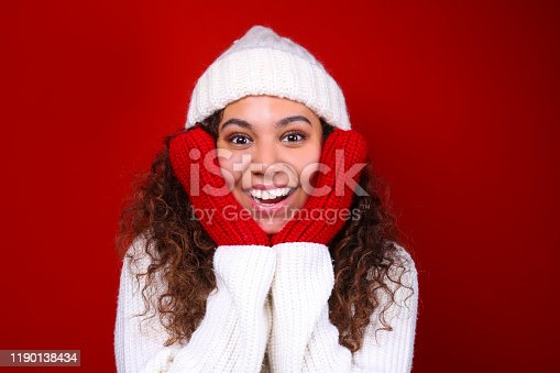 Studio portrait of young woman with dark skin and long curly hair wearing knitted turtle neck sweater over the festive red wall with a lot of copy space for text. Close up, isolated background.