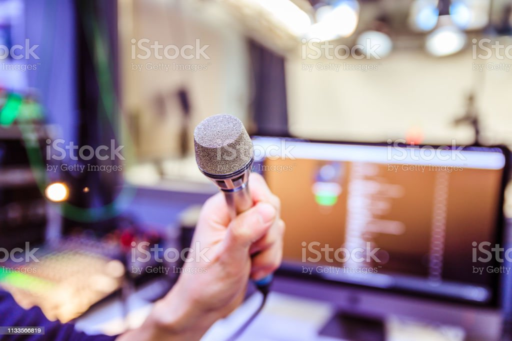 Young man is sitting in the recording studio and talks into the...