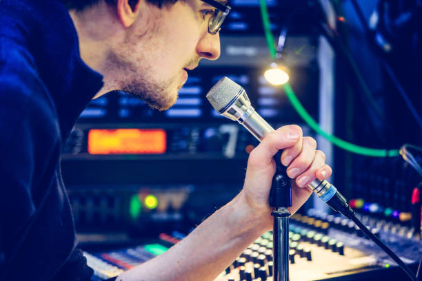 Studio recording: Young man speaks into a microphone, studio in the blurry background stock photo