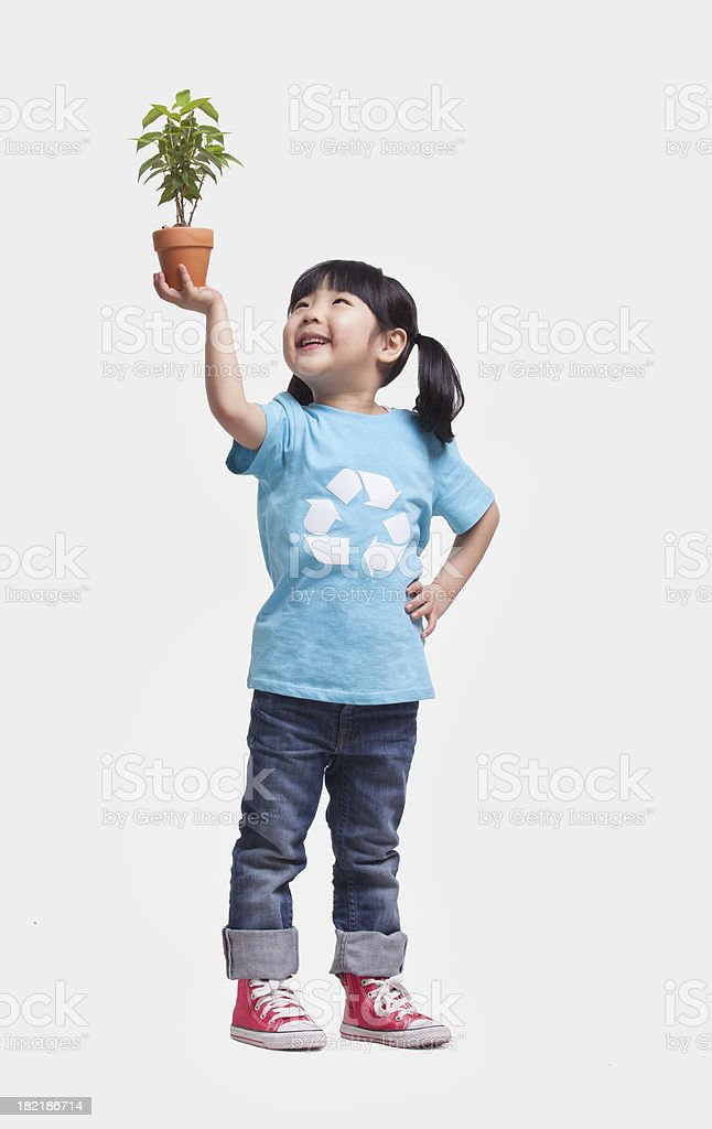 Studio shot little girl holding potted plant over her head stock photo