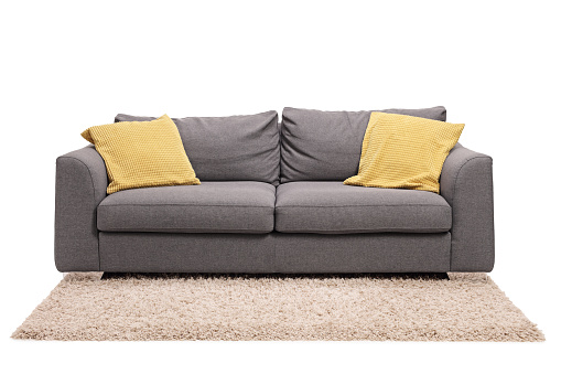 Studio shot of a grey sofa with green pillows on a carpet isolated on white background