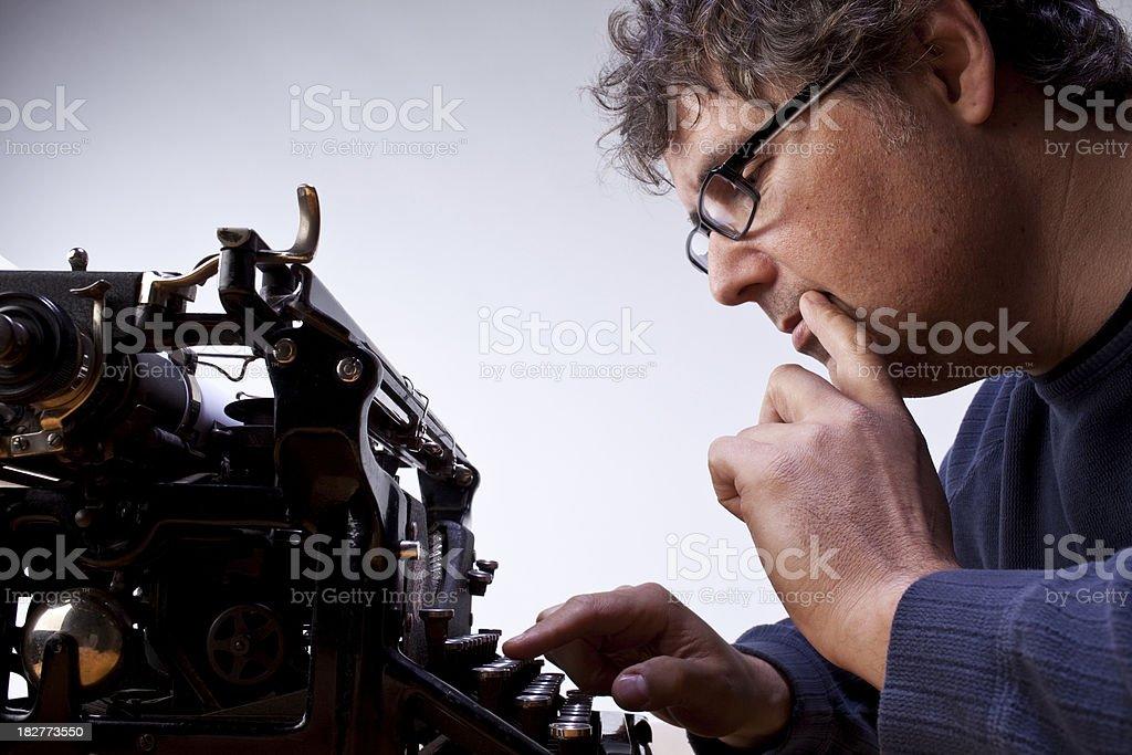Studio shot of a man typing on an old typewriter. royalty-free stock photo