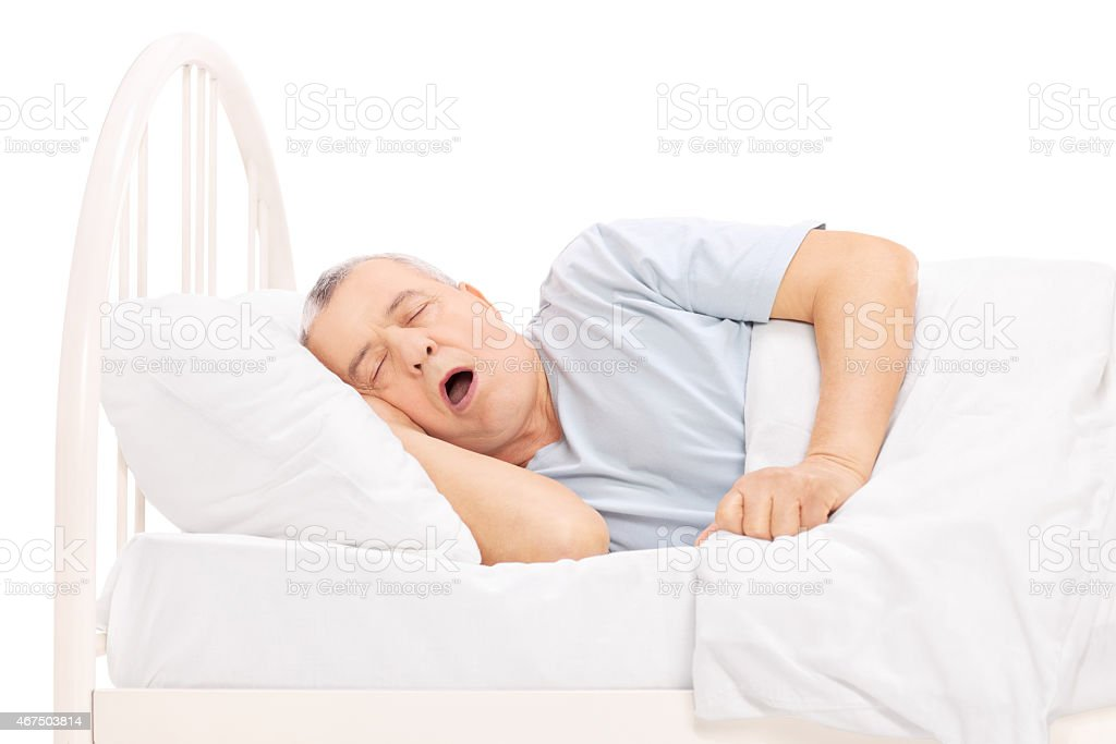 Studio shot of a mature man sleeping in bed stock photo