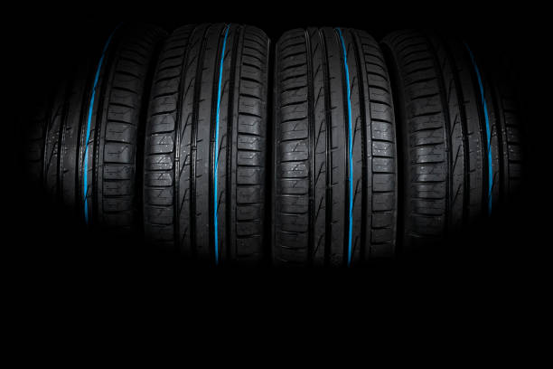 Studio shot of a set of summer car tires on black background. Tire stack background. Selective focus. Car tyre protector close up. Black rubber tire. Brand new car tires. Close up black tyre profile. Car tires in a row stock photo
