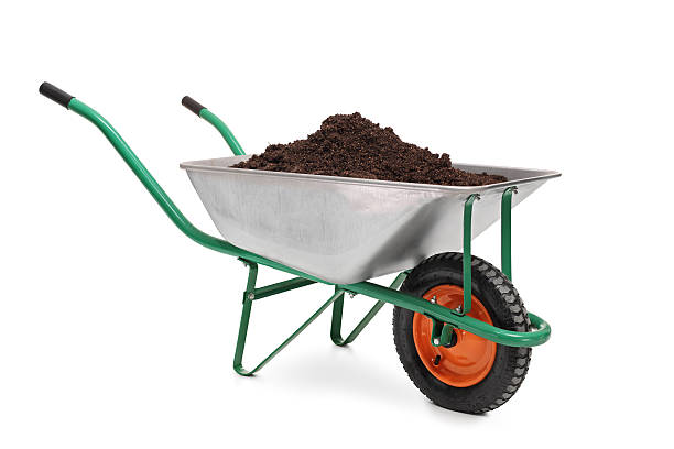 studio shot of a wheelbarrow full of dirt - kruiwagen stockfoto's en -beelden