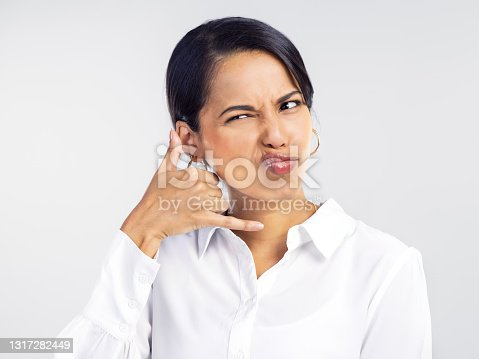 istock Studio shot of a young businesswoman receiving an unwanted call against a grey background 1317282449