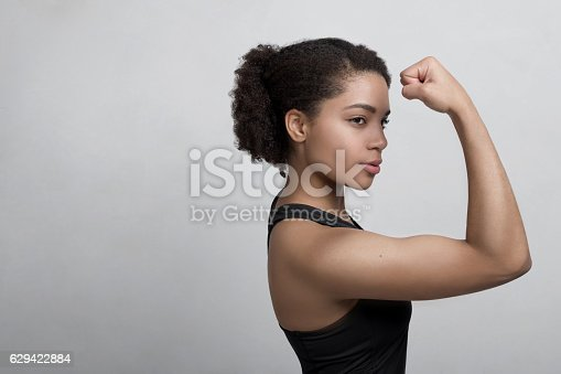 istock Studio shot of a young woman flexing her muscles 629422884