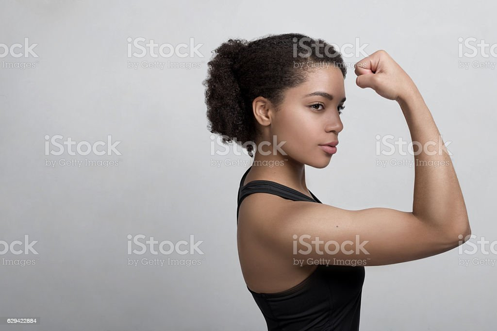 Studio shot of a young woman flexing her muscles - foto de stock