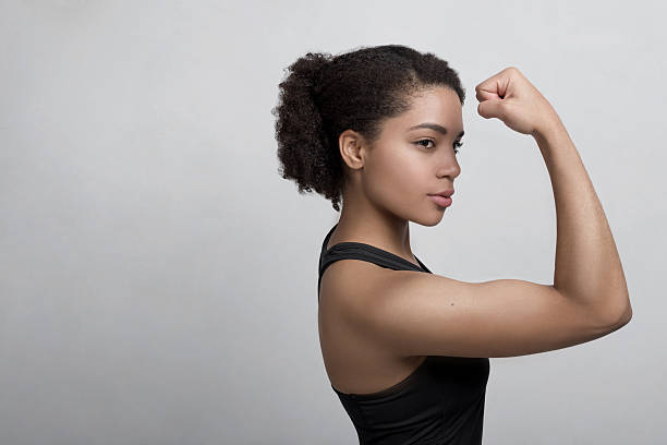 Studio shot of a young woman flexing her muscles stock photo