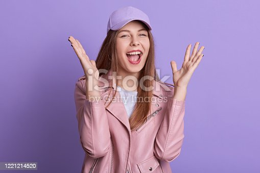 Studio shot of adorable girl screaming happily while posing indoor against lilac wall with palms up, lady wearing rose leather jacket and hat, standing with opened mouth, female expressing joy.