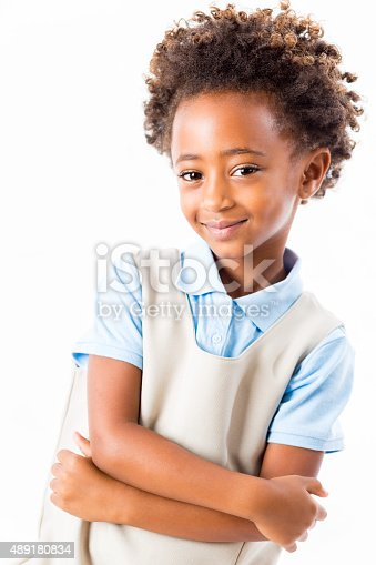Isolated on white waist up studio shot of beautiful elementary age African American girl with curly hair. Cut private elementary school student is wearing a blue and khaki private school uniform and has her arms crossed. She is smiling while looking at the camera.