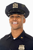 Studio shot of African male police officer smiling