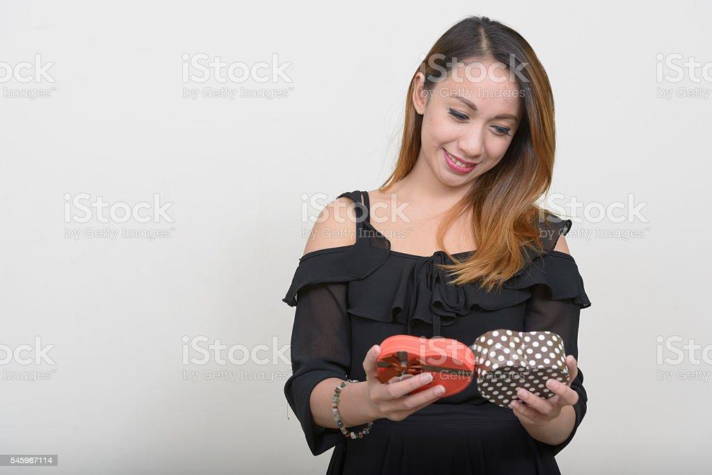 Horizontal studio shot of Asian woman holding heart shaped gift box