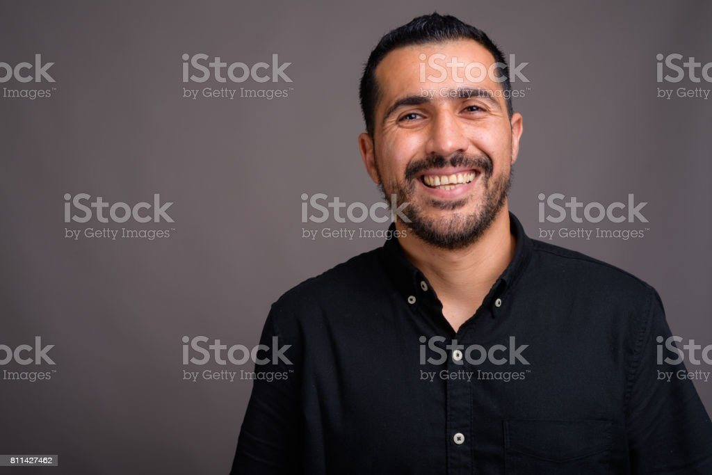 Studio shot of bearded Persian businessman wearing black shirt against gray background stock photo