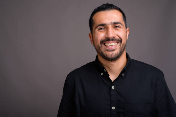 Studio shot of bearded Persian businessman wearing black shirt against gray background stock photo