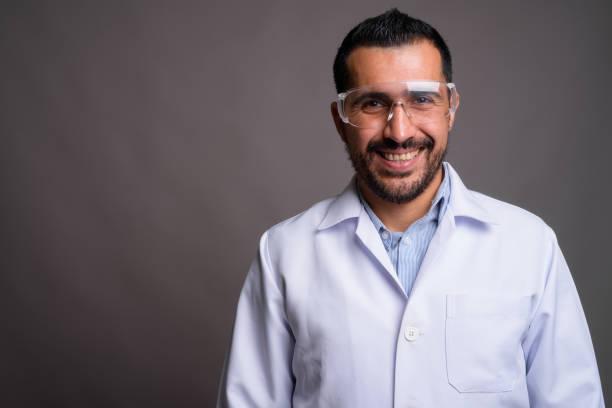 灰色の背景のひげを生やしたペルシャ人医師のスタジオ撮影 ストックフォト